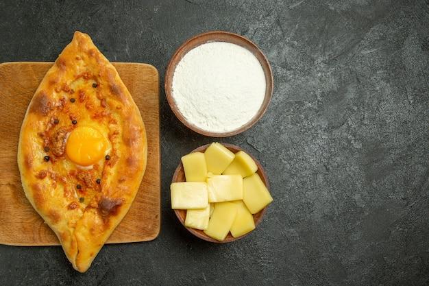 Bovenaanzicht gebakken eierbrood heerlijk deegbroodje vers uit de oven op een donker bureau