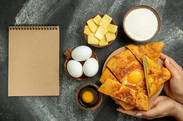 Bovenaanzicht gebakken eierbrood met verse eieren en gesneden kaas op grijze ruimte