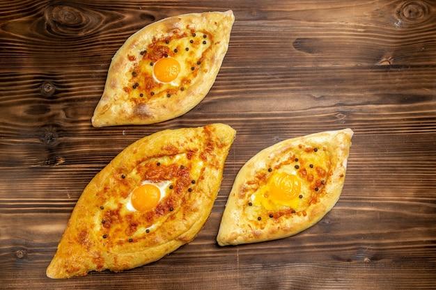 Bovenaanzicht gebakken eierbrood vers uit de oven op bruin bureau deeg eieren brood broodje ontbijt