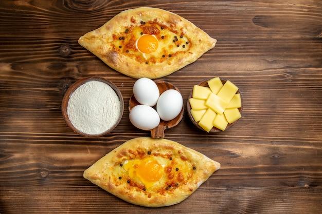 Bovenaanzicht gebakken eierbrood vers uit de oven op bruin houten bureau deeg ei brood ontbijt