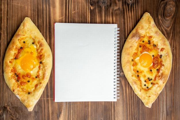 Bovenaanzicht gebakken eierbrood vers uit de oven op bruin houten bureau deeg eieren brood broodje ontbijt