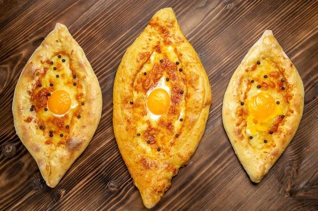 Bovenaanzicht gebakken eierbrood vers uit de oven op het bruine bureau deeg ei brood broodje ontbijt