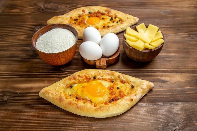 Bovenaanzicht gebakken eierbrood vers uit de oven op het bruine houten bureau deeg ei broodje ontbijt brood