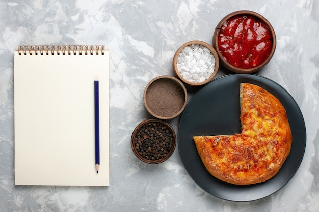 Bovenaanzicht gebakken gesneden pizza met kruiden op wit