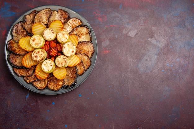 Bovenaanzicht gebakken groenten aardappelen en aubergines in plaat op donker bureau