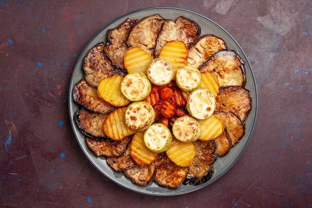 Bovenaanzicht gebakken groenten aardappelen en aubergines in plaat op donkere ruimte