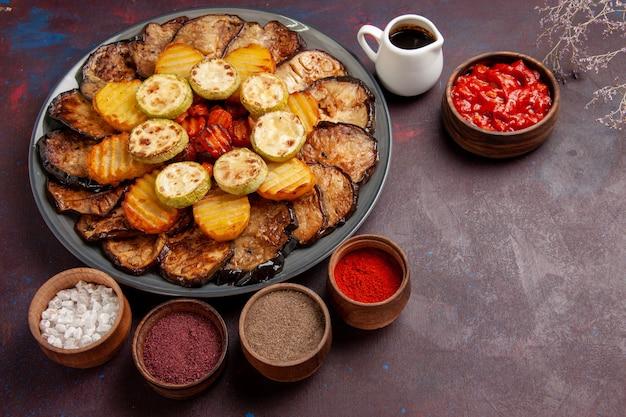 Bovenaanzicht gebakken groenten aardappelen en aubergines met verschillende kruiden op donkere ruimte