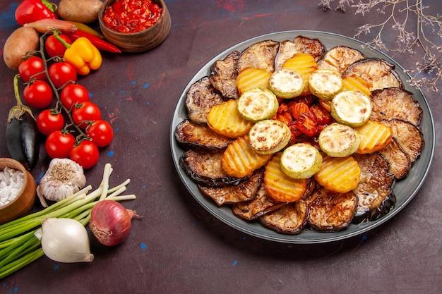 Bovenaanzicht gebakken groenten aardappelen en aubergines met verse groenten op donkere ruimte