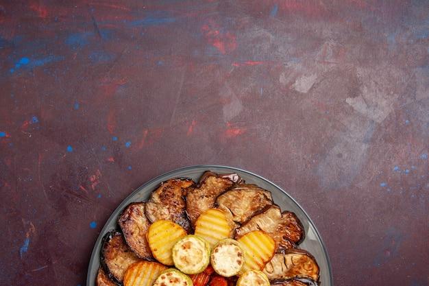 Bovenaanzicht gebakken groenten aardappelen en aubergines vers uit de oven op donkere ruimte
