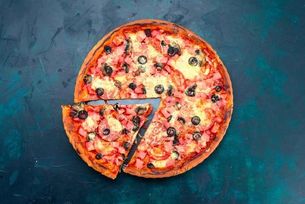 Bovenaanzicht gebakken heerlijke pizza met olijven worstjes en kaas gesneden op blauw bureau.