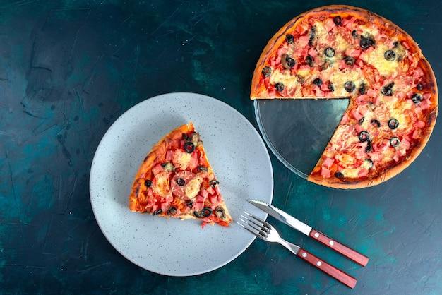 Bovenaanzicht gebakken heerlijke pizza met olijven worstjes en kaas op het blauwe bureau.