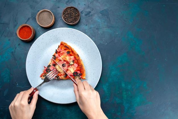 Bovenaanzicht gebakken heerlijke pizza met olijven, worstjes en kaas, samen met kruiden op het blauwe bureau.