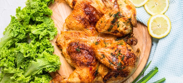 Bovenaanzicht gebakken hele kip met schijfjes citroen en salade