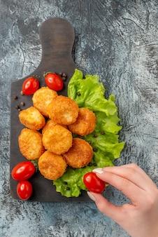 Bovenaanzicht gebakken kaas ballen cherry tomaten sla op snijplank cherry tomaat in vrouwelijke hand