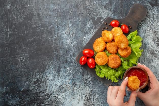 Bovenaanzicht gebakken kaasballetjes, cherrytomaatjes op snijplank, ketchupkom en kaasbal in vrouwelijke handen