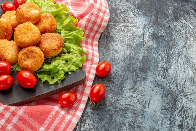 Bovenaanzicht gebakken kaasballetjes cherrytomaatjes op snijplank vrije ruimte