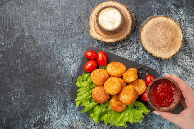 Bovenaanzicht gebakken kaasballetjes op snijplank sauskommen op houten bord