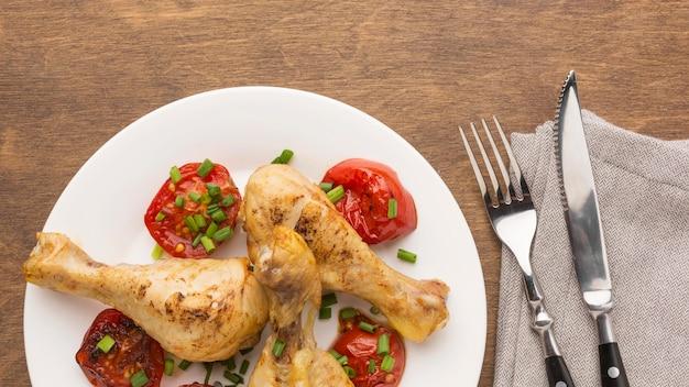 Bovenaanzicht gebakken kip drumsticks en tomaten op plaat met bestek en theedoek