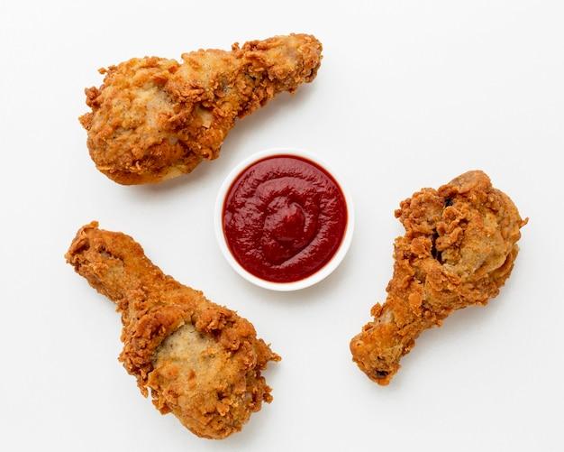 Bovenaanzicht gebakken kip drumsticks met ketchup