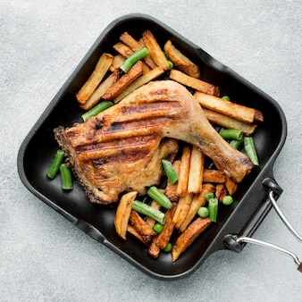 Bovenaanzicht gebakken kip en aardappelen in de pan