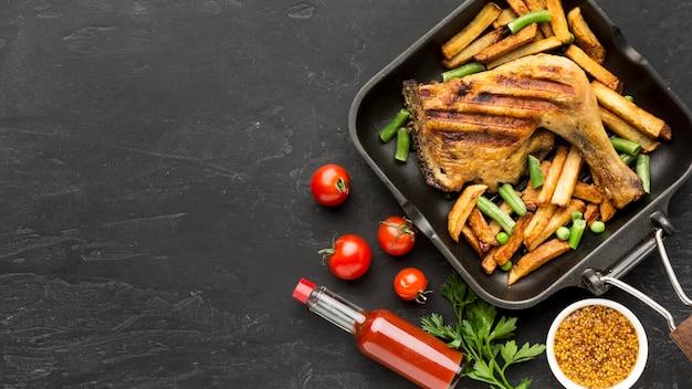 Bovenaanzicht gebakken kip en aardappelen in pan met tomaten en kopie-ruimte