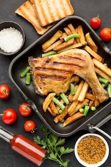 Bovenaanzicht gebakken kip en aardappelen in pan met tomaten en toast