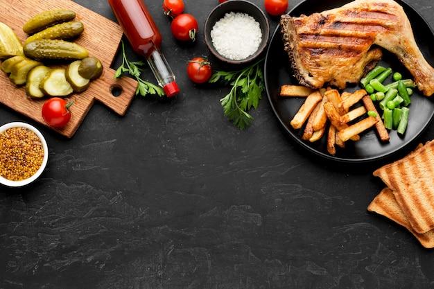 Bovenaanzicht gebakken kip en aardappelen op plaat met augurken en kopie-ruimte