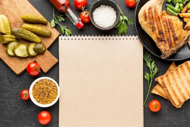 Bovenaanzicht gebakken kip en aardappelen op plaat met augurken en lege blocnote