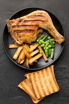 Bovenaanzicht gebakken kip en aardappelen op plaat met toast
