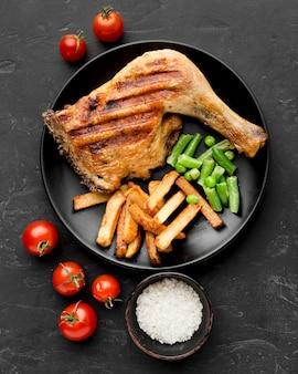 Bovenaanzicht gebakken kip en aardappelen op plaat met tomaten