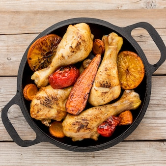Bovenaanzicht gebakken kip en groenten in de pan
