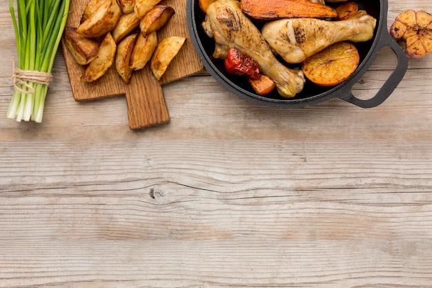 Bovenaanzicht gebakken kip en groenten in pan met aardappelen en kopie-ruimte