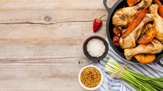 Bovenaanzicht gebakken kip en groenten in pan met kruiden, groene uien en kopie-ruimte