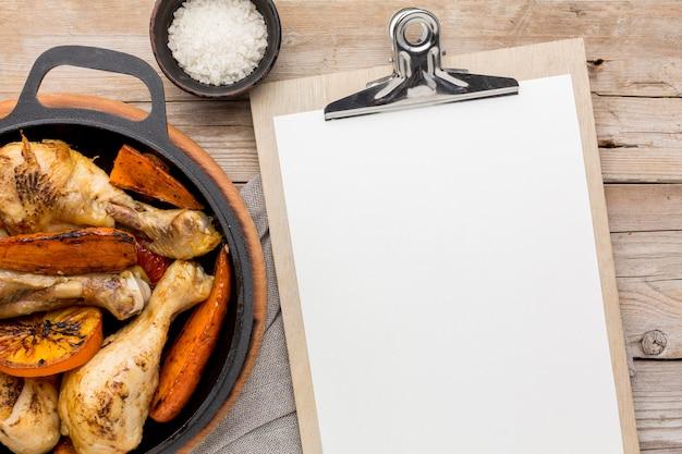 Bovenaanzicht gebakken kip en groenten in pan met leeg klembord