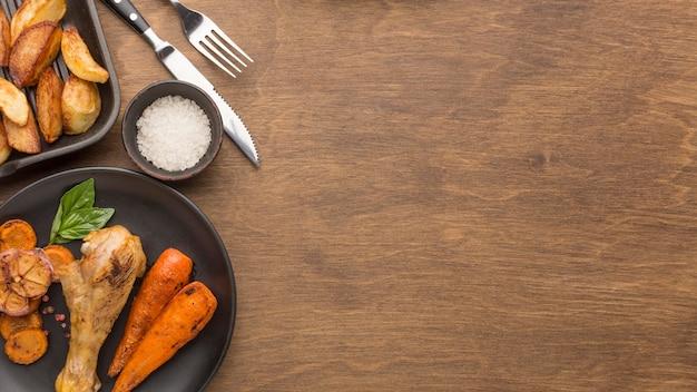 Bovenaanzicht gebakken kip en groenten op plaat met wiggen en kopie-ruimte