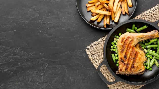 Bovenaanzicht gebakken kip en peulen in pan met aardappelen en kopie-ruimte