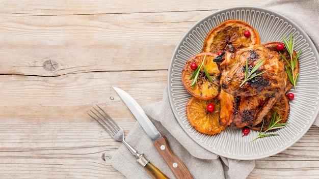 Bovenaanzicht gebakken kip en stukjes sinaasappel op plaat met kopie-ruimte