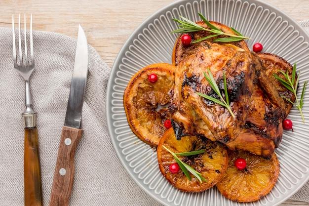 Bovenaanzicht gebakken kip en stukjes sinaasappel op plaat