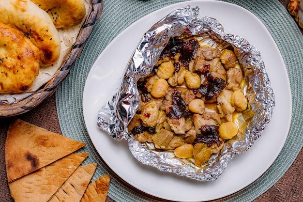Bovenaanzicht gebakken kip in folie met gedroogde vruchten en kastanjes en met brood