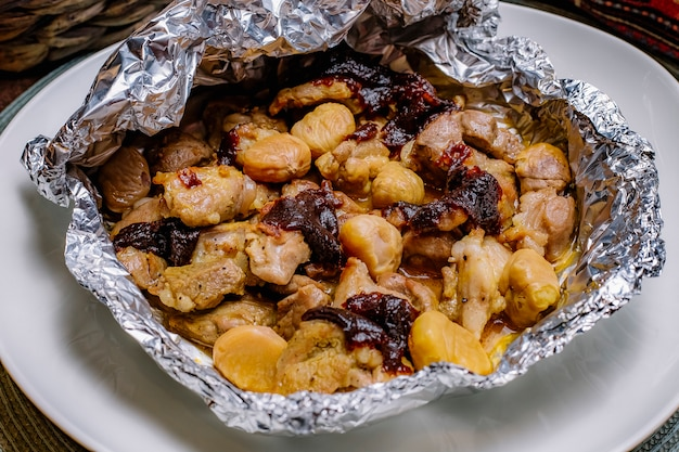 Bovenaanzicht gebakken kip in folie met gedroogde vruchten en kastanjes