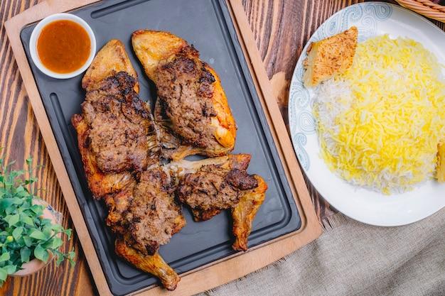 Bovenaanzicht gebakken kip lavangi met saus en rijst