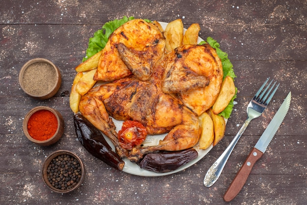 Bovenaanzicht gebakken kip met gekookte groenten en seizoensborden op het donkere houten bureau maaltijd gerecht vlees