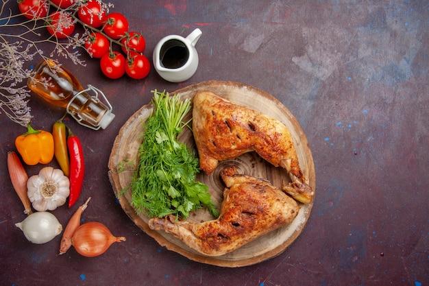 Bovenaanzicht gebakken kip met groenen en groenten op de donkere ruimte
