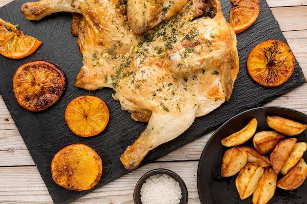 Bovenaanzicht gebakken kip met stukjes sinaasappel en wiggen