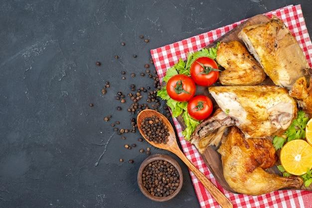 Bovenaanzicht gebakken kip op houten plank zwarte peper in kleine kom houten lepel op zwart