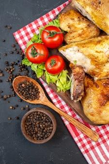 Bovenaanzicht gebakken kip op houten plank zwarte peper in kleine kom houten lepel op zwarte tafel