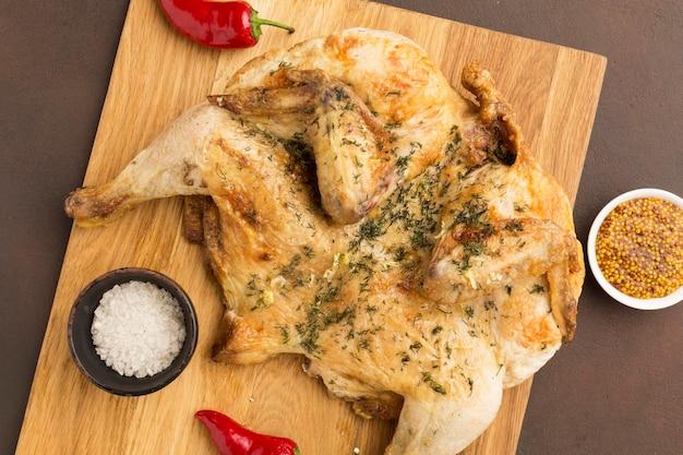 Bovenaanzicht gebakken kip op snijplank met dijon mosterd en rode paprika