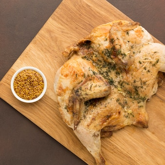 Bovenaanzicht gebakken kip op snijplank met dijon mosterd