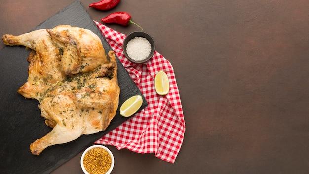 Bovenaanzicht gebakken kip op snijplank met kruiden en kopie-ruimte