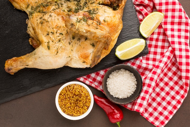 Bovenaanzicht gebakken kip op snijplank met kruiden